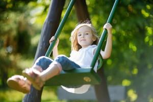 Adorable girl having fun on a swing